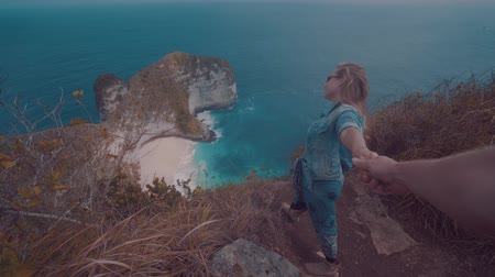 hayran olmak : Girl standing on the cliff and holding boyfriends hand over beautiful Kelingking Beach cliffs background in Nusa Penida, Bali, Indonesia Stok Video