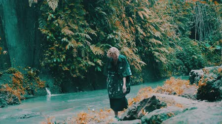 különc : Beautiful fashion girl posing in tropical rain forest jungle near the waterfall. Portrait of stylish hipster female outdoor