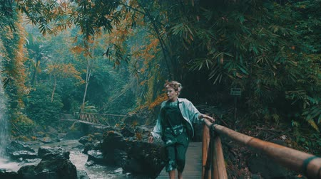 lacuna : Beautiful fashion girl posing in tropical rain forest jungle near the waterfall. Portrait of stylish hipster female outdoor