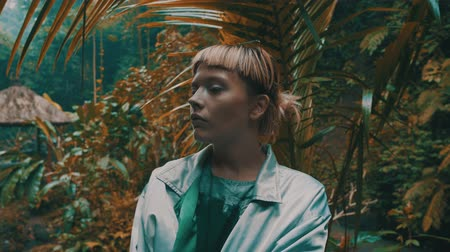 výstřední : Beautiful fashion girl posing in tropical rain forest jungle near the waterfall. Portrait of stylish hipster female outdoor