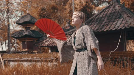výstřední : Beautiful fashion girl in kimono with red hand fan posing outdoor near traditional Balinese temple. Portrait of stylish hipster female outdoor