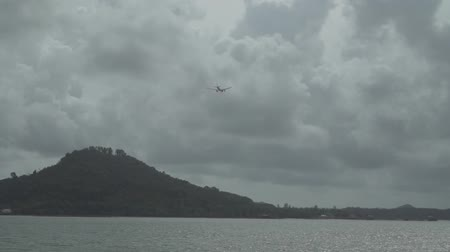 ticker : Airplane flying in the cloudy sky over island Stock Footage