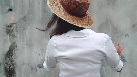saman : Fashion beauty portrait of smiling girl in white dress and straw hat isolated over grey concrete wall Stok Video