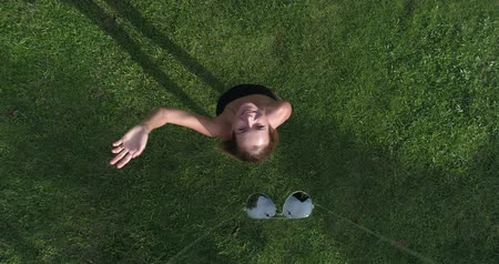 znicz : Aerial top view of happy woman waving to the camera while standing on the grass during sunny summer day. Drone is taking off her sunglasses while coming up - summer relax concept video