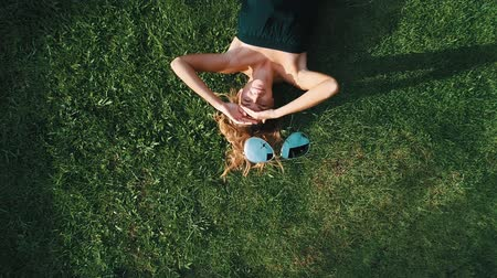 znicz : Aerial top view of happy woman relaxing on the grass during sunny summer day. Drone is taking off her sunglasses while coming up - summer relax concept video