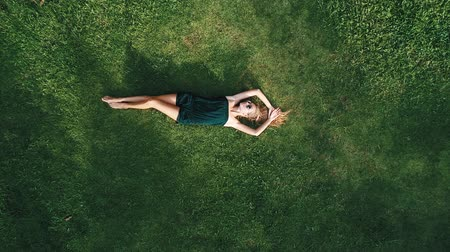 znicz : Aerial top view of happy woman relaxing on the grass during sunny summer day