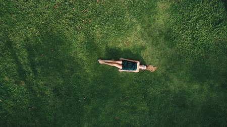 antenas : Aerial top view of happy woman relaxing on the grass during sunny summer day
