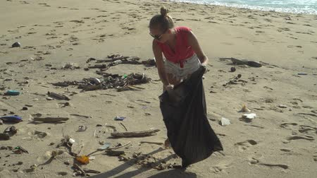 coletando : Woman tourist cleaning the beach on her holiday
