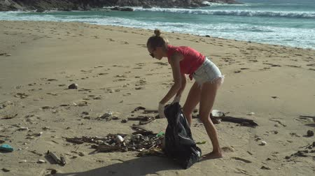 dobrovolník : Woman tourist cleaning the beach on her holiday