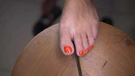barefooted : Closeup of womans foot doing pedicure. Girl applying red nail polish