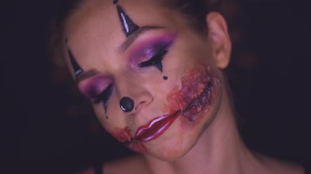děsivý : Closeup face of woman with creepy Halloween clown makeup looking into the camera. Creative, artistic, Halloween concept - video in slow motion