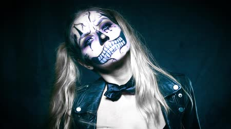 ijesztő : Closeup face of woman with creepy Halloween clown skull makeup looking into the camera. Creative, artistic, Halloween concept - video in slow motion Stock mozgókép