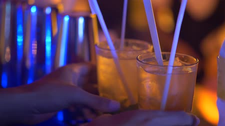 ром : Closeup hands of bartender with prepared Mojito drinks in the bar. Drinks ready to serve to the customers - video in slow motion