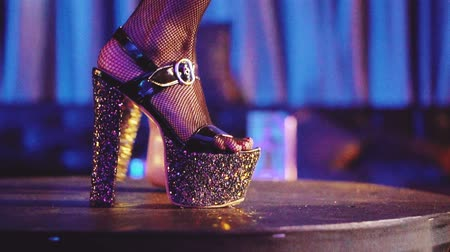 striptease : Closeup of womans legs in high heels dancing in the night club - video in slow motion