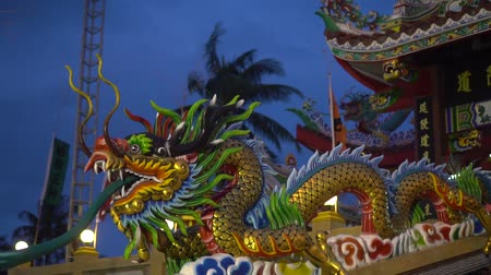crença : Multicolored Chinese dragon against blue sky and palm trees. Beautiful dragon in Chinese temple with the sky and palm trees,Thailand