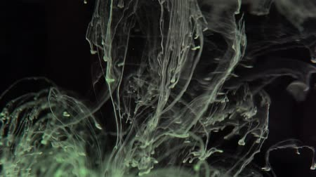laktóz : Closeup green ink being poured into water over black background - video in slow motion