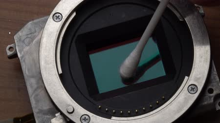 mirrorless : Macro closeup of cleaning cameras sensor with cotton pad - video in slow motion