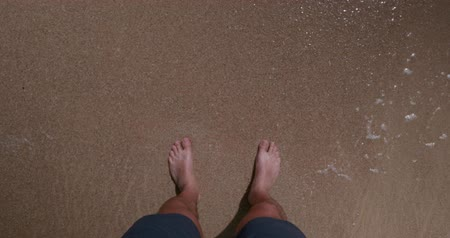 barefooted : Man walking on the sandy beach. Closeup males feet washed by sea waves - first person view shot
