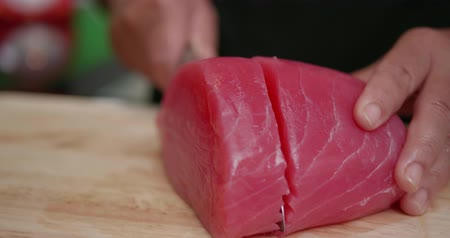prepare food : Closeup womans hands cutting up raw fillet of salmon with sharp knife. Closeup of chef preparing fresh salmon steak on a wooden cutting board - video in slow motion
