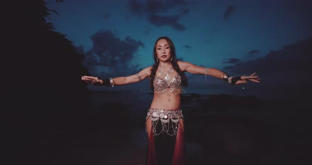 törzsi : Beautiful tribal belly dancer outdoors. Woman in oriental costume dancing near the sea during sunset