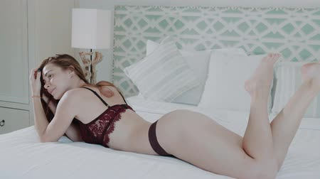 pensamento : Beautiful red hair girl in lingerie posing on bed in modern decor villa house bedroom - video in slow motion