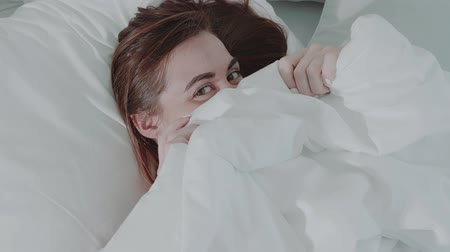 acordar : Closeup face of beautiful red hair girl looking into the camera while playing with bed sheet during morning wake up - video in slow motion