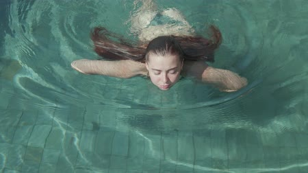 holiday villa : Young pretty woman swimming in the outdoor pool during sunny summer day - video in slow motion