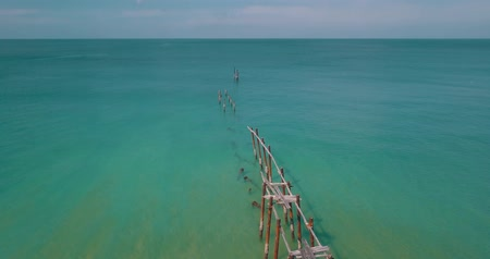 wooden bridge : Aerial drone view of wooden piles stick out in the water of the sea over blue sky background