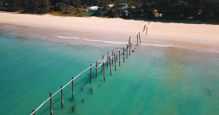 wooden bridge : Aerial drone view of wooden piles stick out in the water of the sea over tropical island beach background Stock Footage