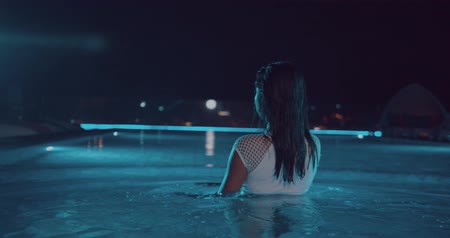 bronzeada : Beautiful woman in white swimsuit walking into the outdoor swimming pool during night - video in slow motion