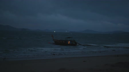 restless : Boat drifting in the wavy sea  over cloudy dark sky background. Cinematic dramatic footage of restless sea water and sky before the storm in early morning