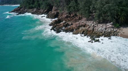 oceanos : Aerial drone view of oceans beautiful waves crashing on the rocky island coast with green trees