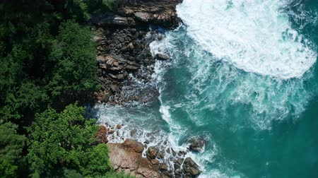 oceanos : Aerial drone top view of oceans beautiful waves crashing on the rocky island coast with green trees