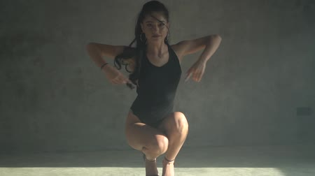 seductive : Beautiful sensual woman in black body suit dancing in hazy studio with grey concrete walls - video in slow motion
