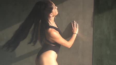 striptease : Beautiful sensual woman in black body suit dancing in hazy studio with grey concrete walls - video in slow motion