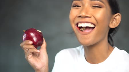 лечение зубов : Portrait of beautiful young smiling woman in white t-shirt eating red apple over concrete background