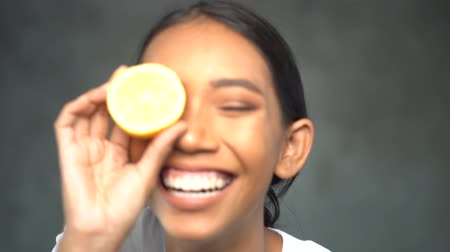 orange t shirt : Portrait of beautiful young smiling woman in white t-shirt holding halves of orange near face over concrete background Stock Footage