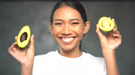 avocado : Portrait of beautiful young smiling woman in white t-shirt holding halves of avocado over concrete background