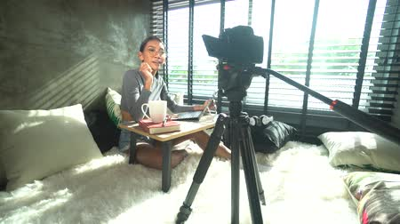 téma : Young smiling woman vlogger talking, showing thumbs up while recording her daily video blog. Beautiful girl vlogger using a camera mounted on a tripod to record her video