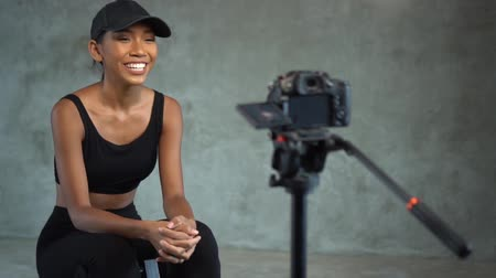 téma : Young smiling woman vlogger talking, showing thumbs up and doing crunches while recording her daily fitness video blog. Beautiful girl vlogger using a camera mounted on a tripod to record her video Dostupné videozáznamy