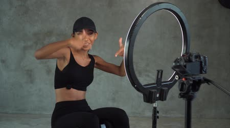 argomento : Young smiling woman vlogger talking, showing thumbs up and doing crunches while recording her daily fitness video blog. Beautiful girl vlogger using a camera mounted on a tripod to record her video Filmati Stock