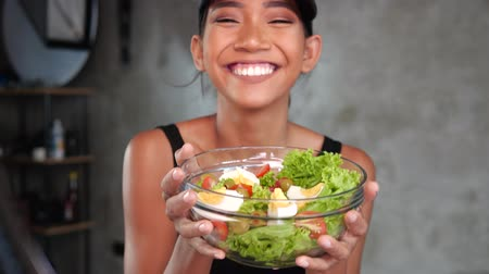 téma : Portrait, of young smiling woman vlogger talking, showing healthy salad while recording her daily fitness diet video blog