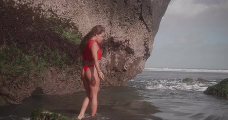 modelka : Sensual brunette girl in red bikini and top posing in the sea water near the rocks - video in slow motion