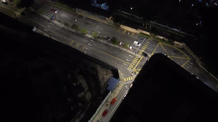 Aerial drone view of night road with moving cars and buildings