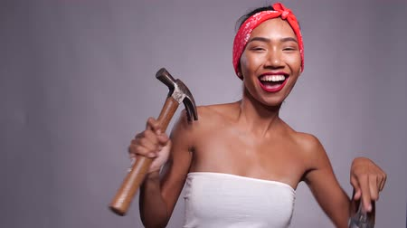 Portrait of happy pretty Asian girl posing with drill and hammer isolated over gray wall background