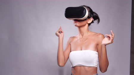 Pretty young Asian girl posing with virtual reality headset or 3d glasses isolated over gray wall background