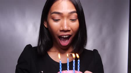 Pretty happy Asian girl blowing candle on birthday cake isolated over gray wall background Стоковые видеозаписи