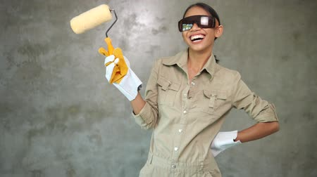Attractive young girl builder with paint roller in uniform, protective glasses and gloves smiling over concrete wall background