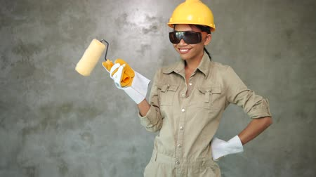 Attractive young girl builder with paint roller in uniform, helmet, protective glasses and gloves smiling over concrete wall background