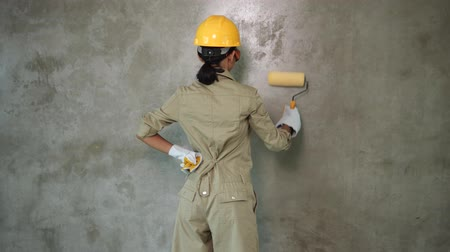 Back view of girl builder with paint roller in uniform, helmet and gloves painting concrete wall Стоковые видеозаписи